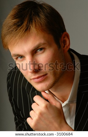 portrait  young serious businessman, looks in  chamber,  close up