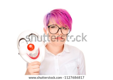 Portrait young upset worried woman with sad expression taking off clown mask expressing cheerfulness happiness isolated on white wall background. Negative facial expressions, human face emotions. #1127686817