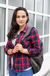 portrait young woman  dark hair plaid shirt backpack looking at the camera