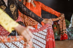 portrait young woman presenting traditional Javanese dance movements being hold shawl