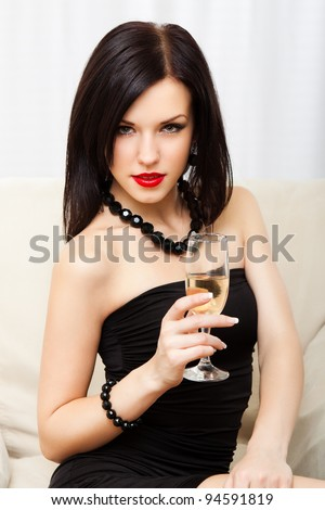 Portrait young woman with glass of champagne, girl with red lips wear evening dress, glamour vogue style, sensual looking at camera, sitting indoors