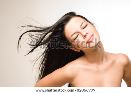 Portraits of a relaxed young brunette with flowing hair.