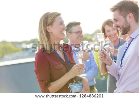 Portraits of an attractive group of businessmen and business women enjoying a glass of wine after an office party or conference convention on a roof terrace bar restaurant to celebrate an event