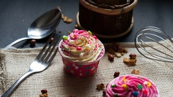 Portraits of Cupcakes on sackcloth with cute colorful seeds and chips topping. Close-up shots with fork, spoon and whisk in blurred.