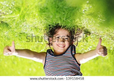 Portraits of happy kid playing upside down outdoors in summer park with thumbs up #139158458