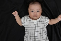 Portraiture image of Three month old Asian Cute little baby boy lsolated on Black