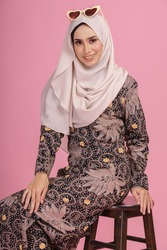 Portraiture of beautiful young Muslim girl wearing dark brown dress known as Baju Kurung with hijab sitting on a chair isolated over pink background. Fashion for dinner, event and Eidul fitri feast.