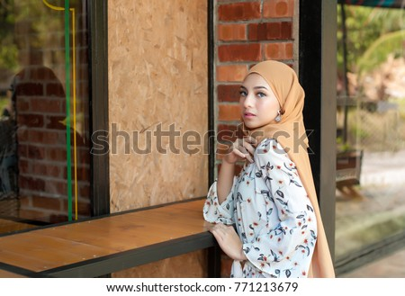 Portraiture of young arabic muslim woman in head scarf smile posing for a camera with cafe background, 20s age. #771213679