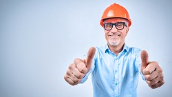 Portraiy of smiling adult architect showing thumb up and looking at camera, isolated on blue background. Construction and design concept