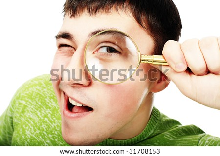Portrat of a young man looking through the magnifying glass - stock photo