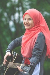 Portreit of happy muslim girl wearing hijab trying to play guitar outdoor