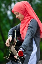 Portreit of preaty muslim girl wearing hijab trying to play guitar outdoor