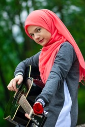 Portreit of preaty muslim woman trying to play guitar