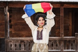 Portret of a beautiful young woman posing in romanian traditional costume in the village museum in winter with the Romanian flag in her hand.