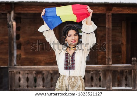 Portret of a beautiful young woman posing in romanian traditional costume in the village museum in winter with the Romanian flag in her hand. Stockfoto ©