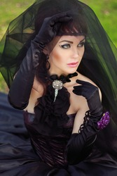 Portret of the dark bride in a black dress, gloves and veil