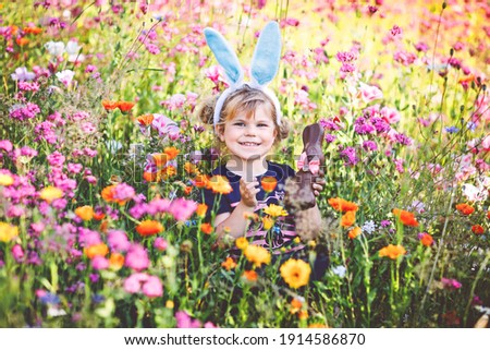 Portriat of adorable, charming toddler girl with Easter bunny ears eating chocolate bunny figure in flowers meadow. Smiling happy baby child on sunny day with colorful flowers, outdoors. Stock foto ©