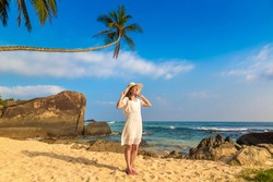 Portriat of young beautiful woman wearing a hat and white dress staying on a tropical beach near sea