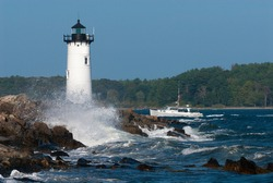 Portsmouth harbor lighthouse, also known as Fort Constitution light, guides a fishing boat through rough seas into the harbor in seacoast New Hampshire. A favorite tourist attraction in New England.