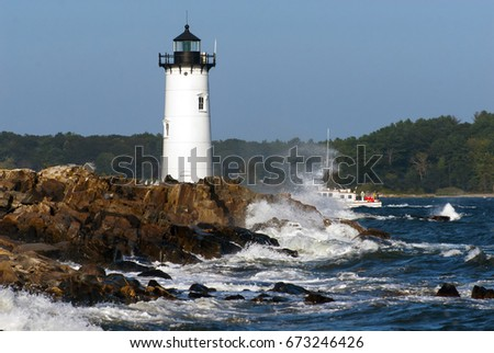 Portsmouth Harbor Lighthouse guides fishing boat amid crashing waves away from the dangerous rocky shore.