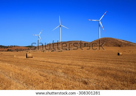Portugal, Alentejo Region, Wind power turbines in an autumn crop field against a deep blue sky.