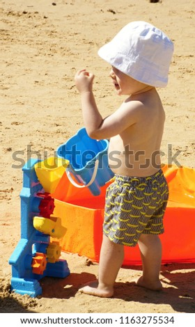 Portugal,Algarve,Armacao 14.08.2018 Little boy is playing in the sand on the beach #1163275534