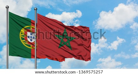 Portugal and Morocco flag waving in the wind against white cloudy blue sky together. Diplomacy concept, international relations. #1369575257