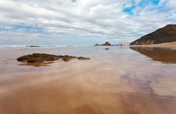 Portugal. Beautiful seascape of the sandy Praia da Castelejo beach in the Algarve on the shores of the Atlantic Ocean. Clouds are reflected in the wet sand at low tide. Natural seaside background