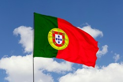 Portugal flag isolated on the blue sky with clipping path. close up waving flag of Portugal. flag symbols of Portugal.