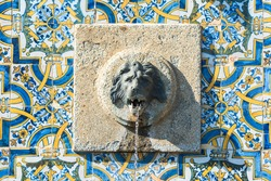 Portugal, fountain with azulejos and head of lion sculptured in the stone