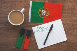 portugal national flag, notebook to write foreign words, inscription speak portuguese in portuguese, two markers, pen on brown wooden desktop, learning concept
