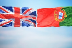 Portuguese and British flags amid blue skies