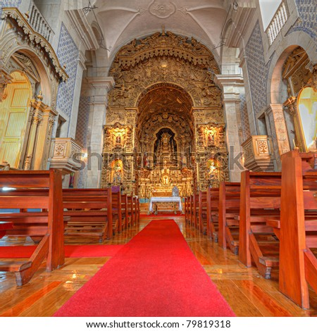 portuguese catholic church with wooden benches azulejos tile interior, lavish golden altar and red carpet, Porto, Portugal