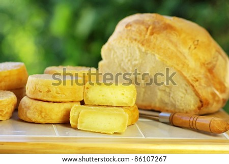 Portuguese cheese, knife and bread. - stock photo