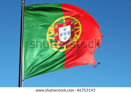 Portuguese national flag blown and torn by the strong sea wind with blue sky as backgroung