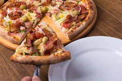 Portuguese Pizza made with ham, pea egg, heart of palm, pepperoni, onion and mozzarella and bacon. Slice of pizza served on the plate. Photo of restaurants and pizzerias