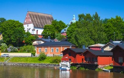 Porvoo old town, summer landscape. Old red wooden houses and trees on the river coast in Finland
