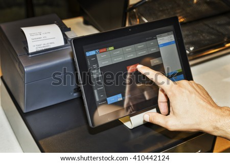POS terminal in coffee cafe waiter\'s hand when serving customers and touching screen of a tablet with software interface to take order and print receipt.