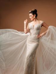 Posh lace wedding dress. Gorgeous model bride in luxury mermaid wedding gown. Brunette lady on golden studio background.