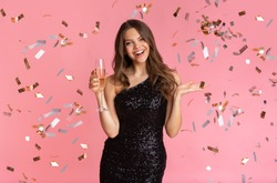 Posh Party. Glamour Woman In Sequin Evening Dress Standing With Glass Of Champagne Under Falling Confetti, Pink Background