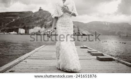 Posing bride at pier by the sea. Wedding picture in black and white.