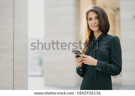 posing for a portrait of a young female student of Caucasian appearance, a brunette in a stylish green dress. smiling and looking at the camera, typing to a friend on a new phone.