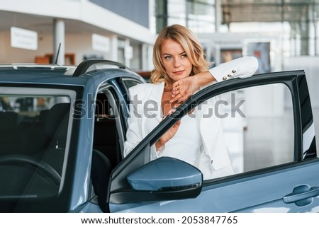 Posing for the camera. Woman in formal clothes is indoors in the autosalon.