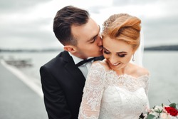 Posing for the camera. Young wedding couple. Romantic Married Couple. The bride and groom stand leaning against each other. The bride with a wreath of  and a bouquet. ?edhed bride haired young