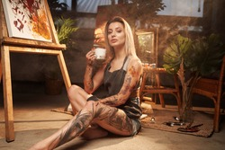 Posing in dark and atmospheric studio room beautiful tattooed and grimy woman holding coffee cup and looking at camera.