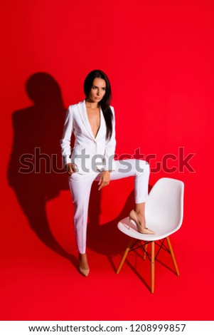 Stock Photo Posing snap portrait of skinny fit woman putting leg on chair looking away wearing white suit with sexual decollete isolated on bright red background. Photoshooting studio concept