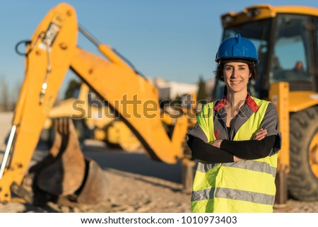 Posing woman looking at camera with hardhat and excavator shovel in background