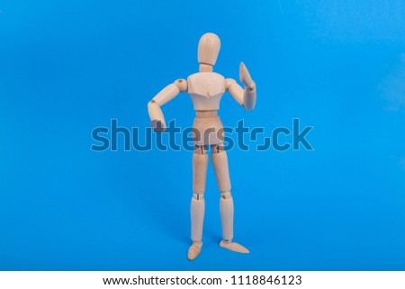 Posing wooden jointed mannequin sketching model figure posed on solid blue background #1118846123