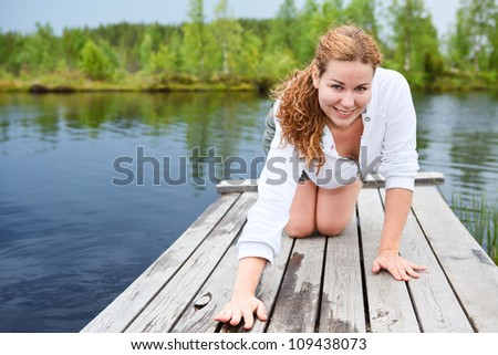 Posing young woman on wooden planks of pond pier. Copyspace - stock photo