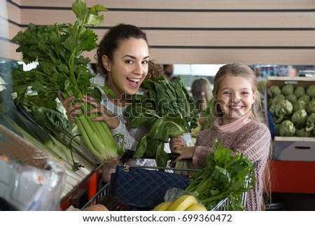 posinive mother and blonde daughter buying greenery in shop